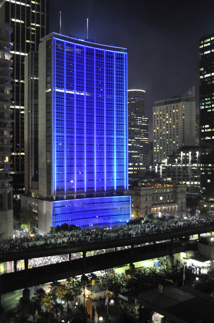 Blue-lit AMP Building with crwods along Cahill Expressway
